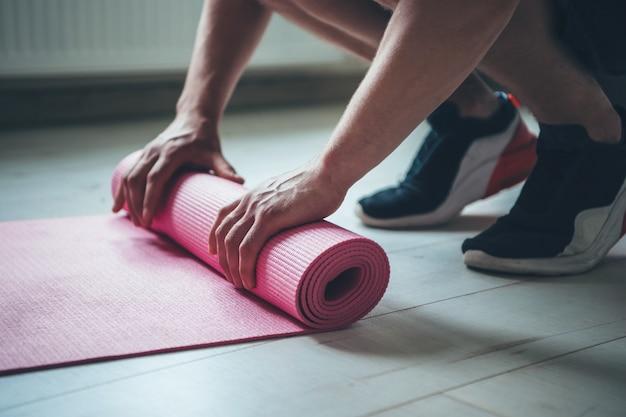 Blanke man in sportkleding is de fitnessles afronden en het tapijt van de vloer verzamelen