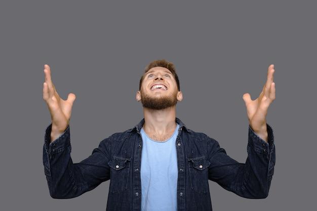 Blanke man kijkt omhoog en dankt god voor iets terwijl hij zich voordeed op een grijze studiomuur met vrije ruimte