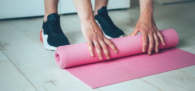 Blanke man klaar met zijn yogales het verzamelen van het tapijt na het sporten thuis