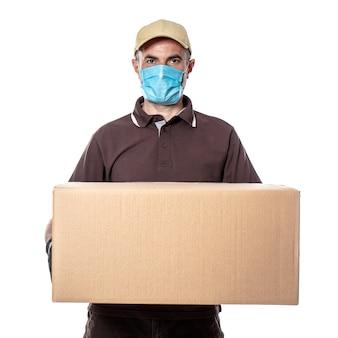 Blanke man koerier met masker en groot te bezorgen pakket. verzendingen tijdens de coronaviruspandemie