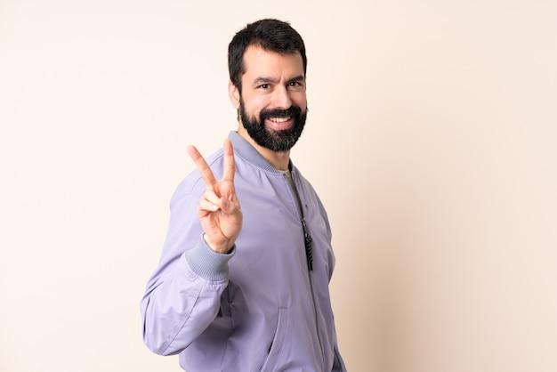 Blanke man met baard die een jas draagt over een geïsoleerde achtergrond die lacht en een overwinningsteken toont