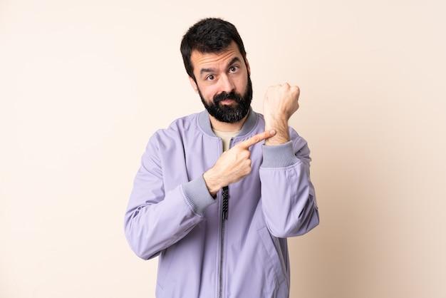 Blanke man met baard die een jas draagt over geïsoleerde achtergrond die het gebaar maakt om te laat te zijn