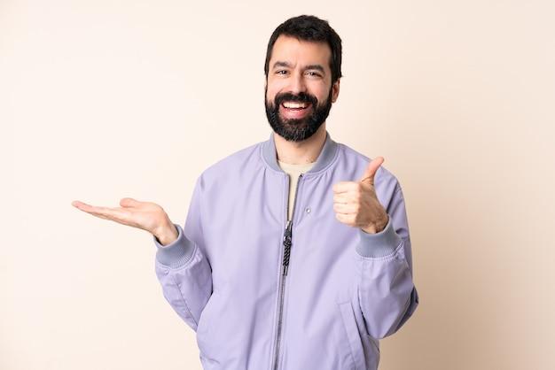 Blanke man met baard die een jas over geïsoleerde muur draagt die copyspace denkbeeldig op de palm houdt om een advertentie in te voegen en met omhoog duimen