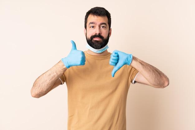 Blanke man met baard die met een masker en handschoenen over muur beschermt die goed-slecht teken maakt