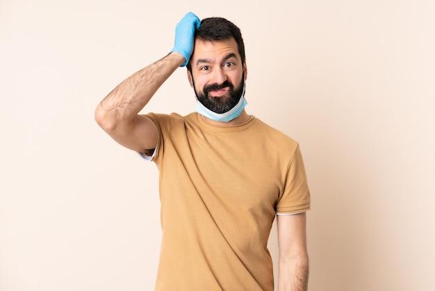 Blanke man met baard die met een masker en handschoenen over muur beschermt met een uitdrukking van frustratie en niet begripvol