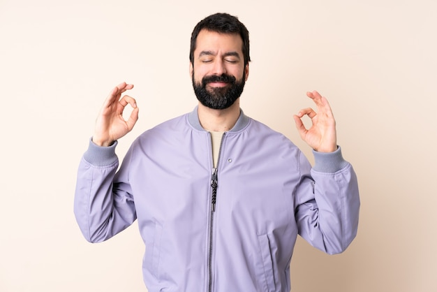 Blanke man met baard draagt een jas over geïsoleerde achtergrond in zen pose