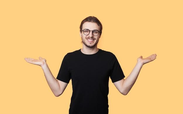 Blanke man met baard en bril vergelijkt twee dingen op zijn handpalm terwijl hij lacht op een gele muur