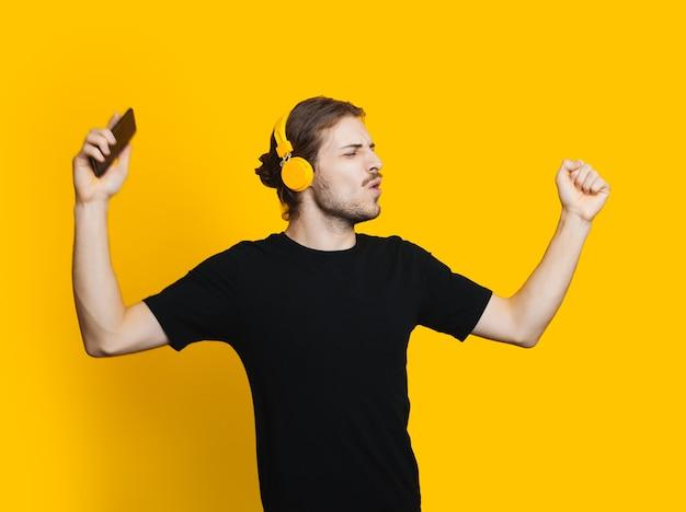 Blanke man met baard en lang haar is dansen tijdens het luisteren naar muziek via een koptelefoon