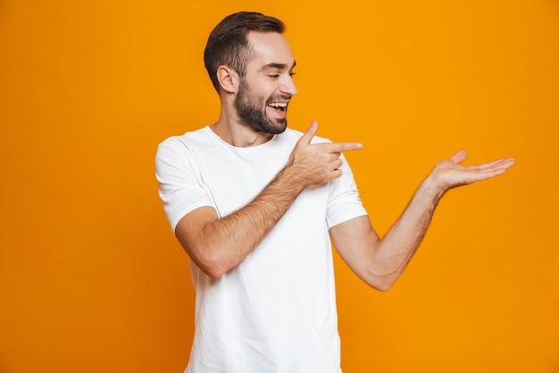 Blanke man met baard en snor copyspace tonen op palm terwijl staande, geïsoleerd op geel