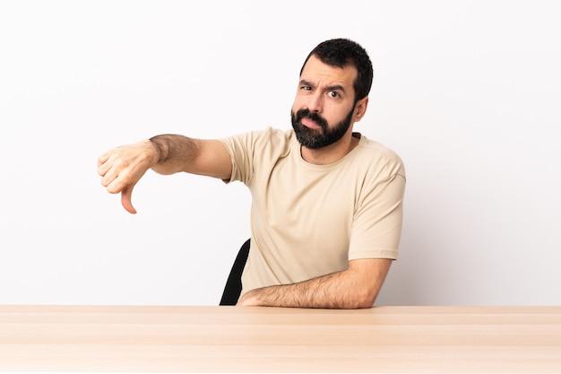 Blanke man met baard in een tabel met duim omlaag met negatieve expressie