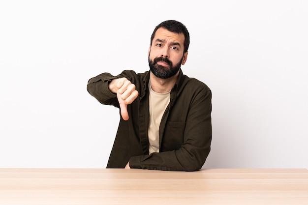 Blanke man met baard in een tabel met duim omlaag met negatieve uitdrukking.