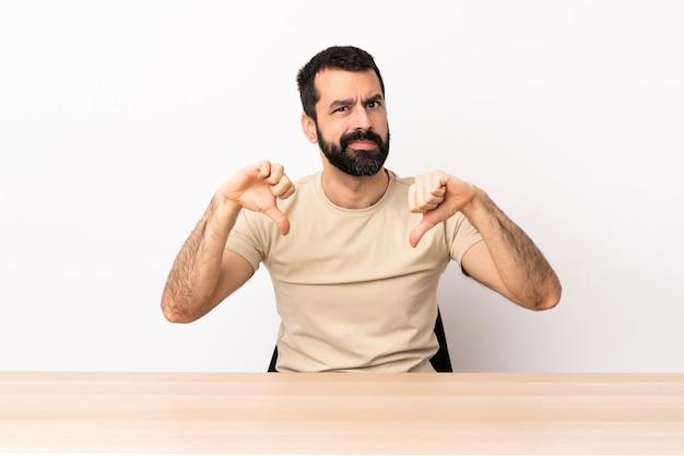 Blanke man met baard in een tabel met duim omlaag met twee handen