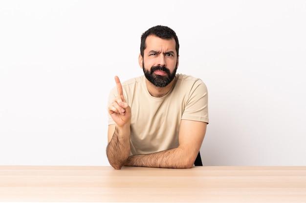 Blanke man met baard in een tabel met een ernstige uitdrukking.