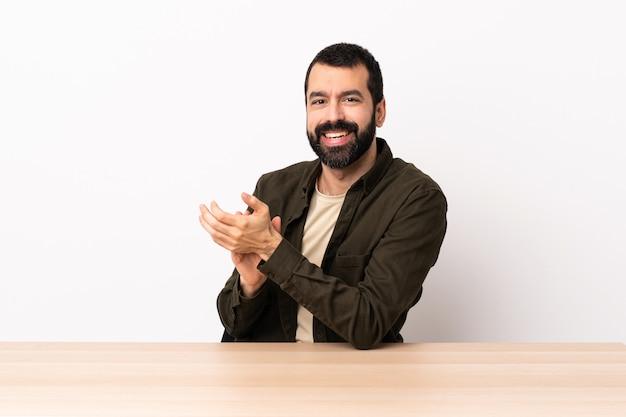 Blanke man met baard in een tafel applaudisseren