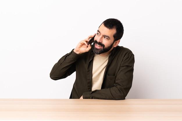 Blanke man met baard in een tafel die een gesprek met de mobiele telefoon met iemand houdt.