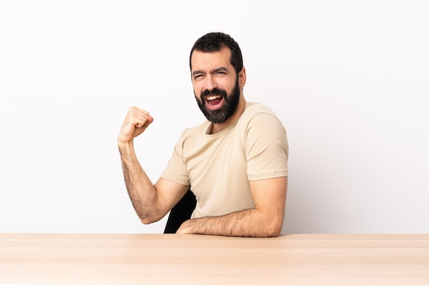 Blanke man met baard in een tafel die een overwinning viert.