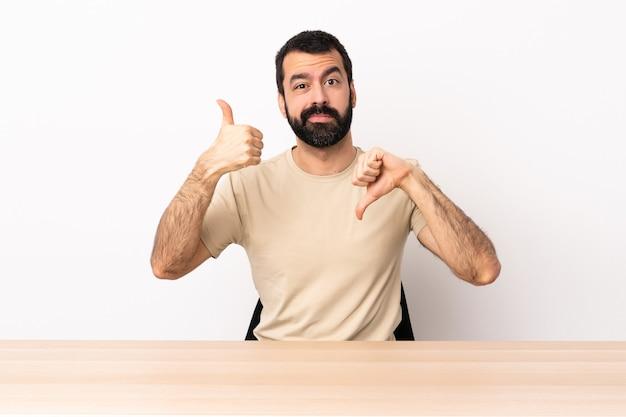 Blanke man met baard in een tafel die goed-slecht teken maakt. onbeslist tussen ja of niet.