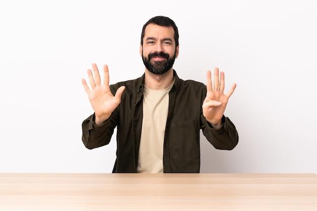 Blanke man met baard in een tafel die negen met vingers telt.