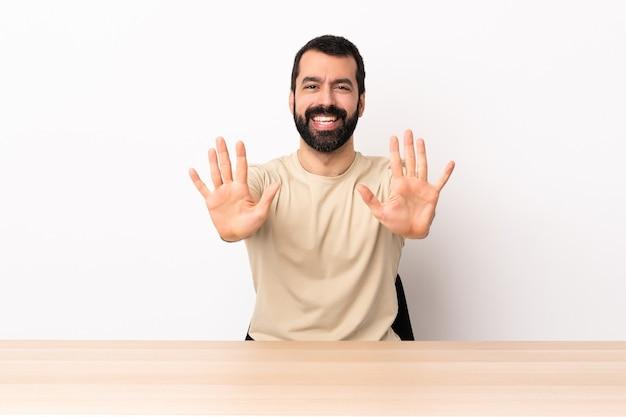 Blanke man met baard in een tafel die tien met vingers telt.