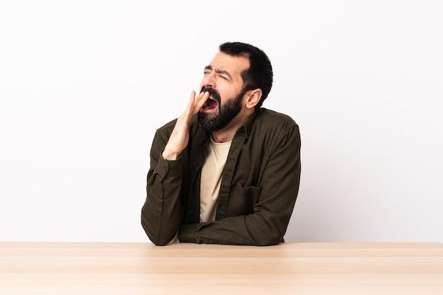 Blanke man met baard in een tafel geeuwen en die wijd open mond met de hand bedekken.