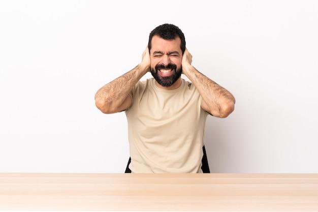 Blanke man met baard in een tafel gefrustreerd en oren bedekken.