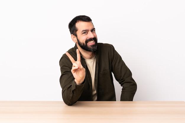 Blanke man met baard in een tafel glimlachend en overwinningsteken tonen.