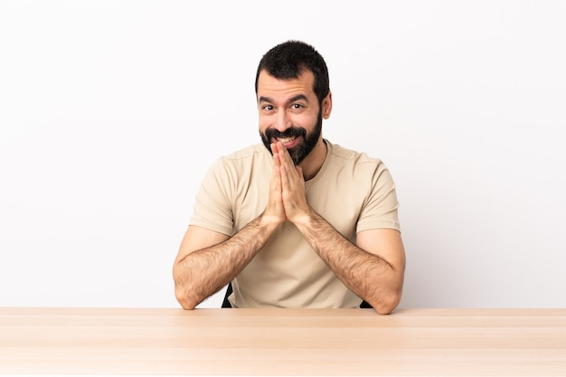 Blanke man met baard in een tafel houdt de palm bij elkaar. persoon vraagt iets.