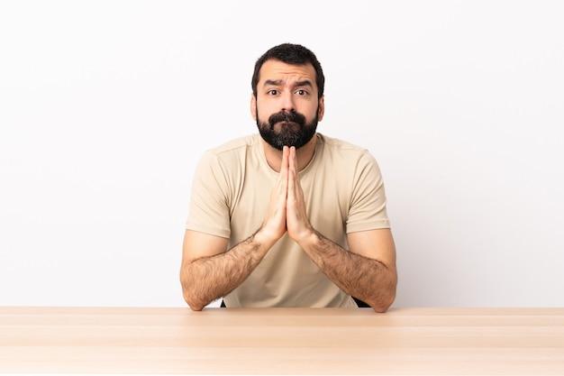 Blanke man met baard in een tafel houdt palm bij elkaar. persoon vraagt iets.