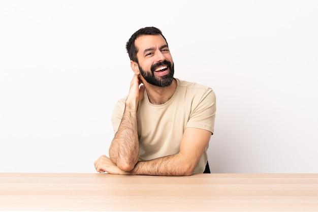Blanke man met baard in een tafel lachen.