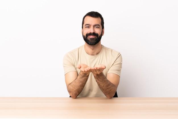 Blanke man met baard in een tafel met copyspace denkbeeldig op de handpalm om een advertentie in te voegen.
