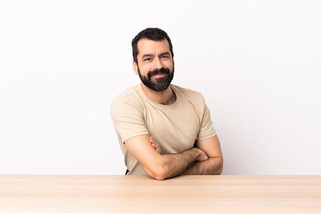 Blanke man met baard in een tafel met gekruiste armen en kijken ernaar uit.