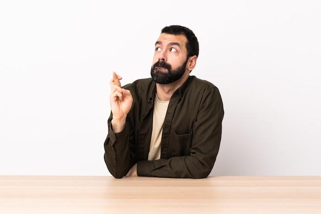 Blanke man met baard in een tafel met vingers die kruisen en het beste wensen.