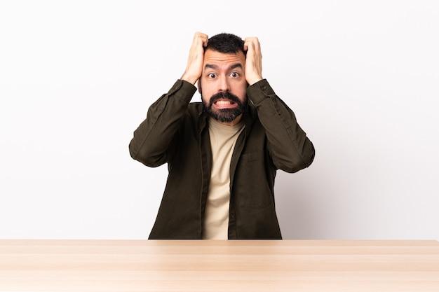 Blanke man met baard in een tafel nerveus gebaar doen.