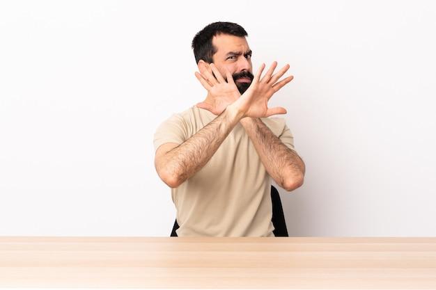Blanke man met baard in een tafel nerveus handen naar voren strekken.