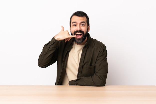 Blanke man met baard in een tafel telefoon gebaar maken. bel me terug teken.