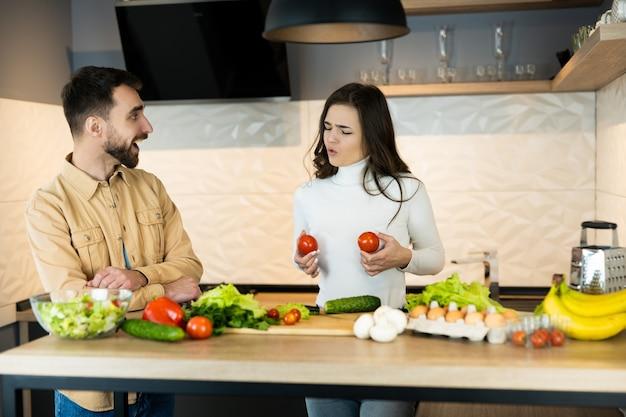 Blanke man met baard lacht en heeft plezier in de keuken met zijn vrouw die voor de gek houdt.