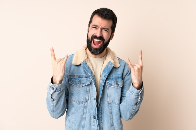 Blanke man met baard over geïsoleerde achtergrond die hoorngebaar maakt