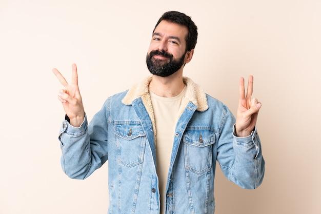 Blanke man met baard over geïsoleerde achtergrond met overwinningsteken met beide handen