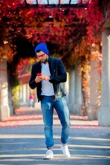 Blanke man met behulp van een mobiele telefoon in een park