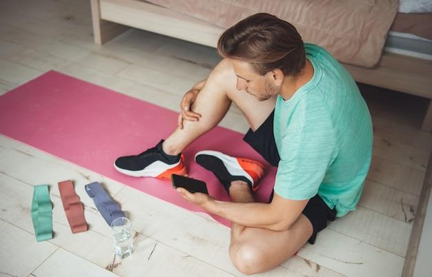 Blanke man met blond haar die sportkleding draagt, zoekt op de telefoon naar thuisfitnesslessen voordat hij begint met trainen