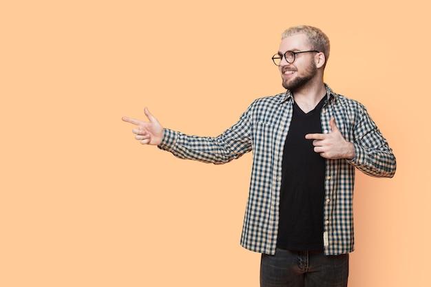 Blanke man met blond haar en baard draagt een bril en wijst op een gele muur met vrije ruimte