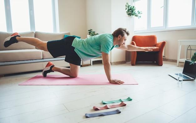 Blanke man met blond haar in activewear is planking en strekt zich uit over een roze yoga tapijt thuis met behulp van een laptop