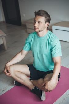 Blanke man met blond haar is aan het mediteren op de vloer, het dragen van sportkleding en het gebruik van yogatapijt