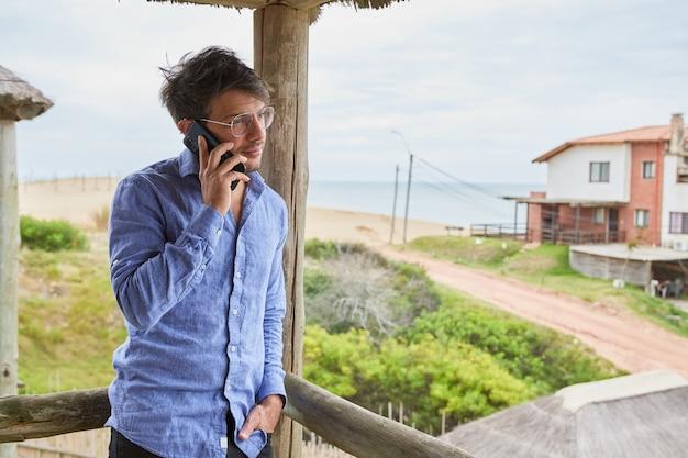 Blanke man met bril praten op zijn smartphone op het terras van zijn strandhut. op de achtergrond zie je het zand en de zee.