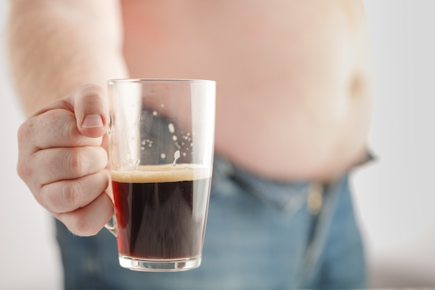 Blanke man met dikke bierbuik, met een glas donker bier. jeans zijn erg strak