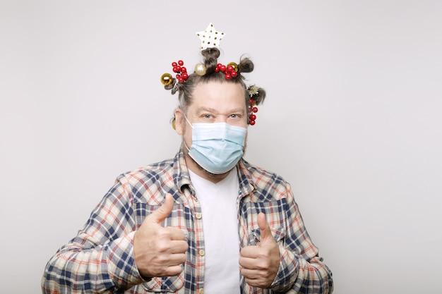 Blanke man met een baard en een versierd kerstkapsel en covid-masker