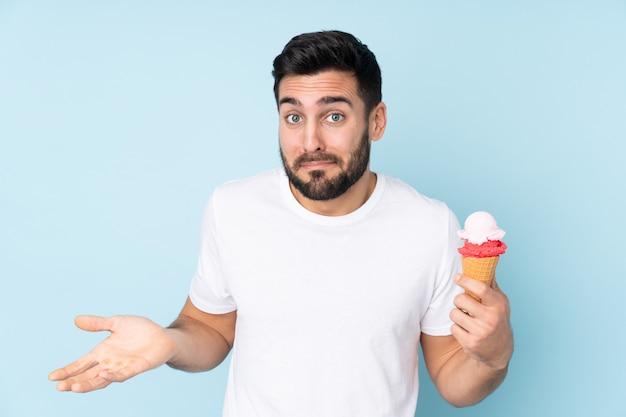 Blanke man met een cornet ijs op blauwe muur twijfels gebaar maken terwijl het opheffen van de schouders Premium Foto