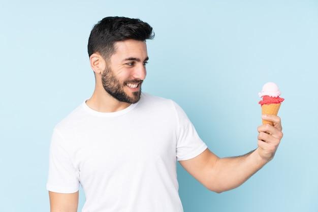 Blanke man met een cornet-ijsje dat op blauwe muur met gelukkige uitdrukking wordt geïsoleerd