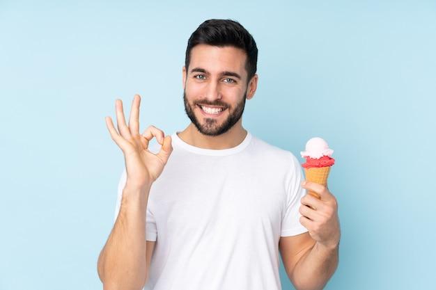 Blanke man met een cornet-ijsje dat op blauwe muur wordt geïsoleerd die ok teken met vingers toont