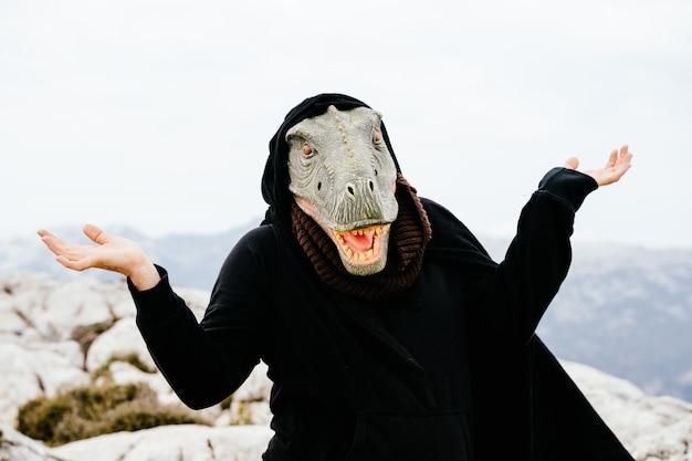 Blanke man met een dinosaurusmasker en een cape die het ik weet het niet-gebaar maakt in de sierra de tramuntana, palma de mallorca, spanje
